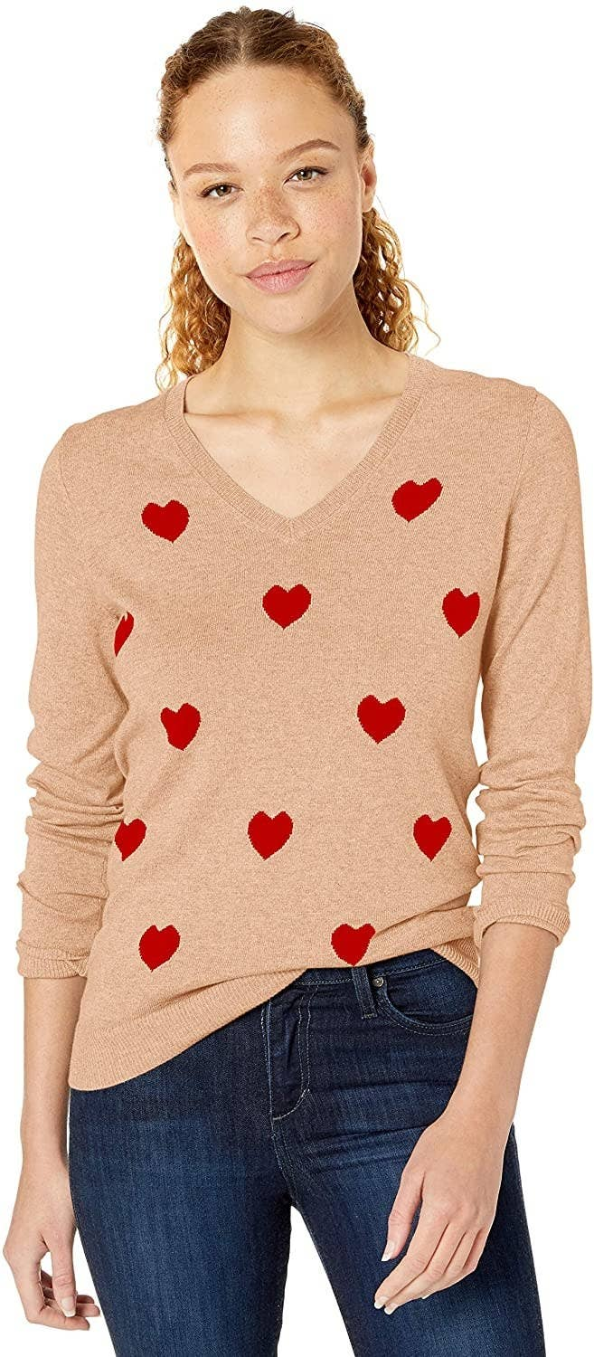 Model wears tan sweater with red hearts and dark wash jeans