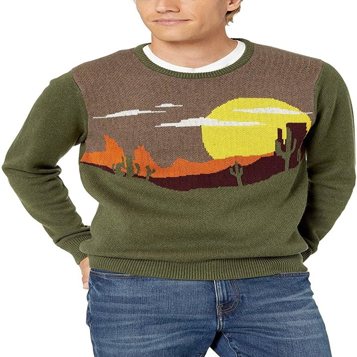 Model wears green, orange and brown southwest landscape sweater with midwash jeans