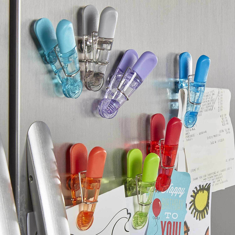 A bunch of magnetic clips stuck to a fridge door