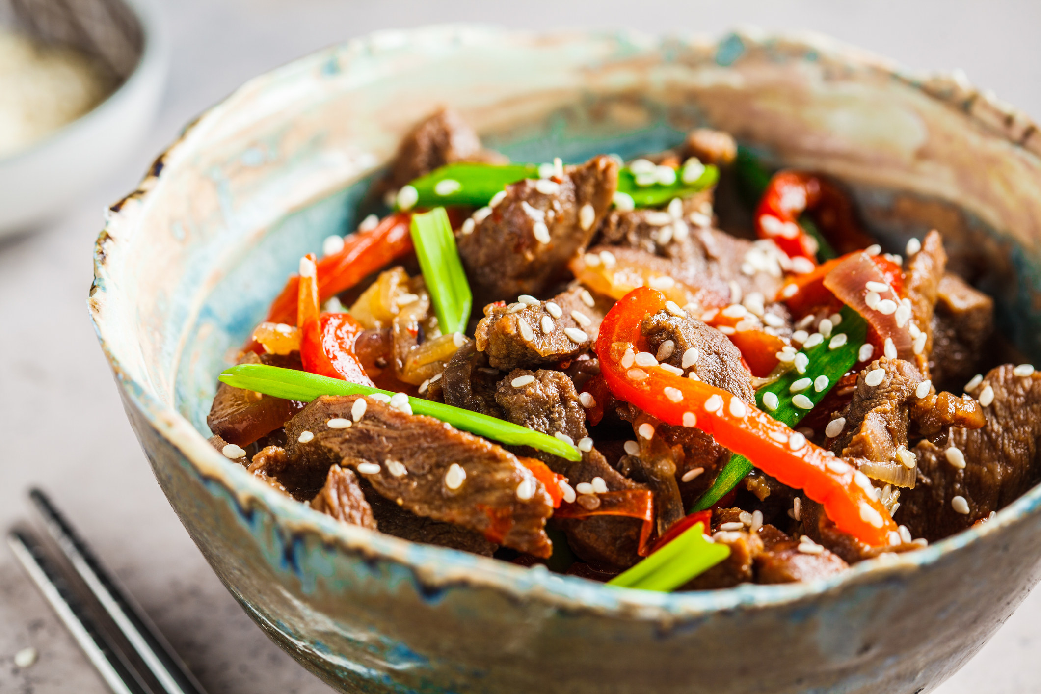 A bowl of steak stir fry with peppers.