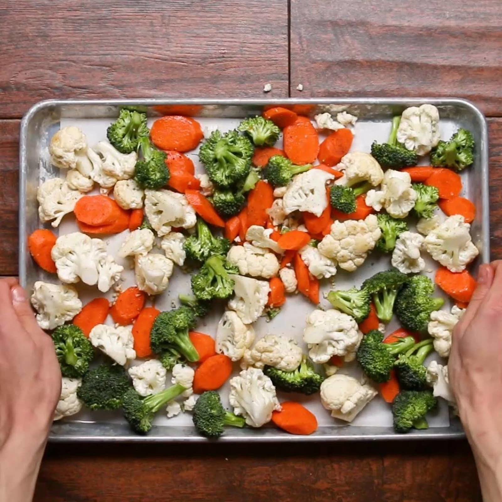 Cauliflower, broccoli, and carrots on a sheet pan.