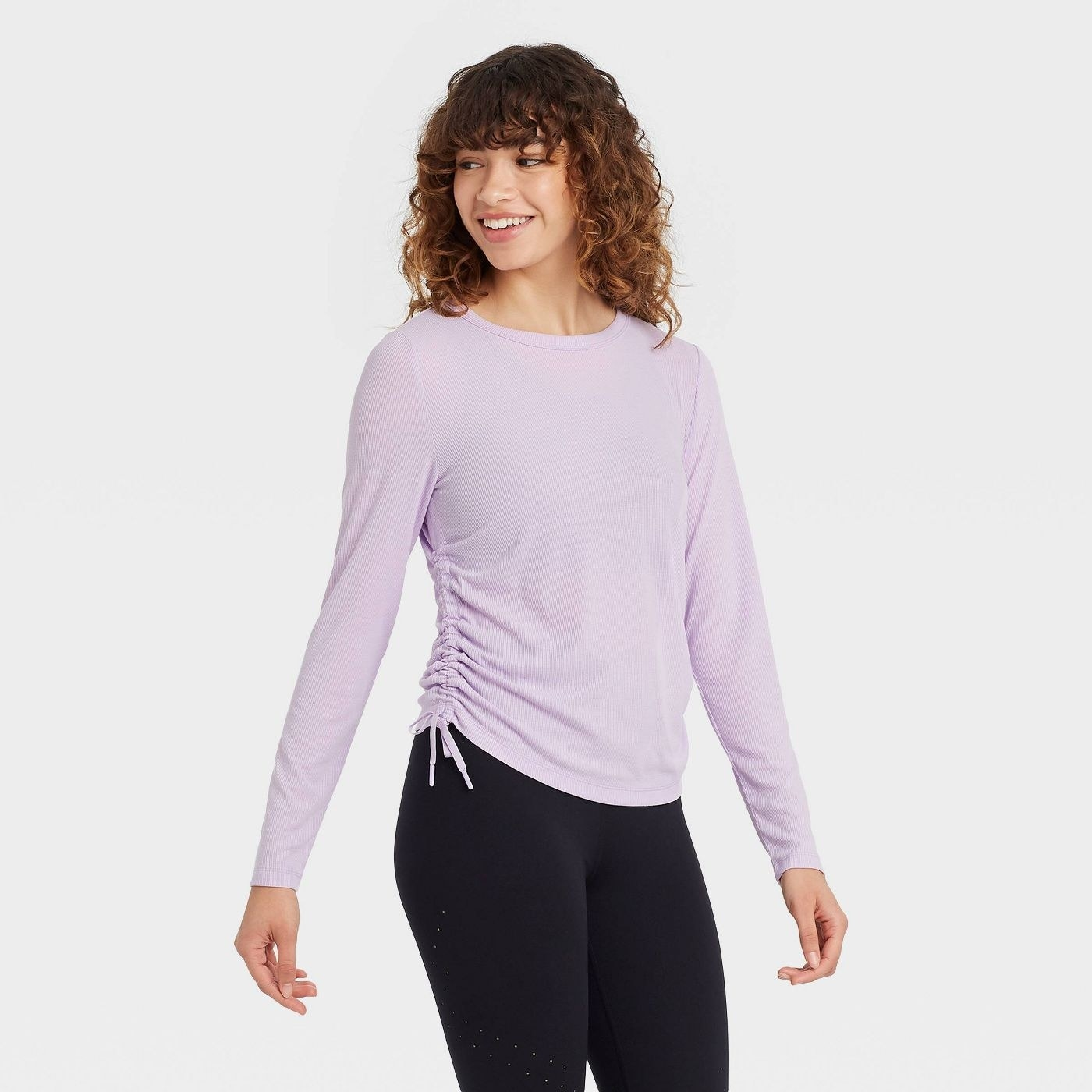 Model in long sleeve top with side cinch detail