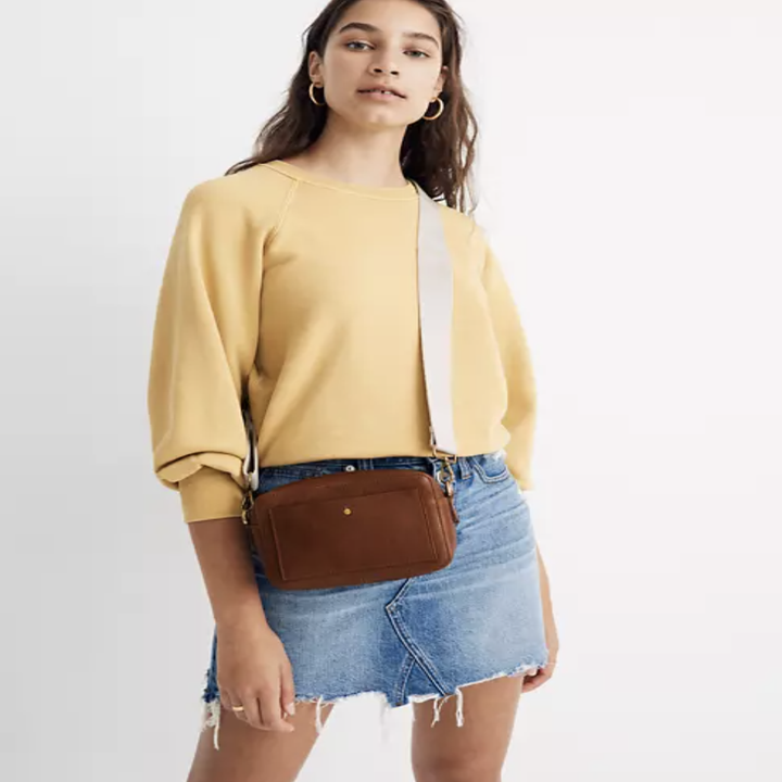 model wears brown camera crossbody bag with white strap