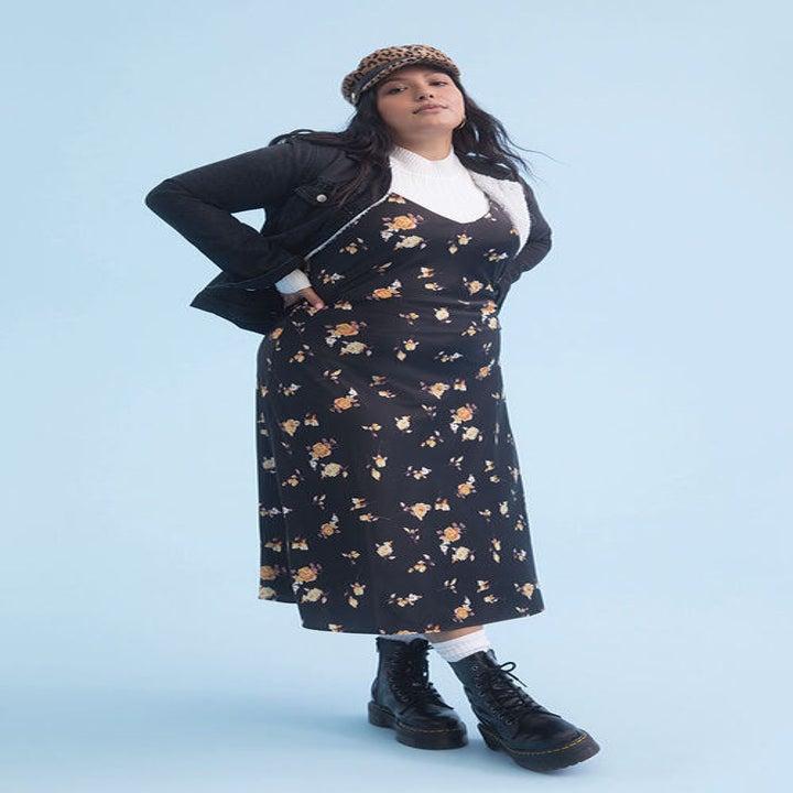 model in v-neck black floral midi dress, white turtleneck, and combat boots
