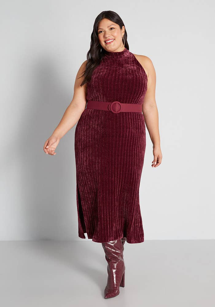 model in sleeveless merlot midi dress with thigh-high red boots