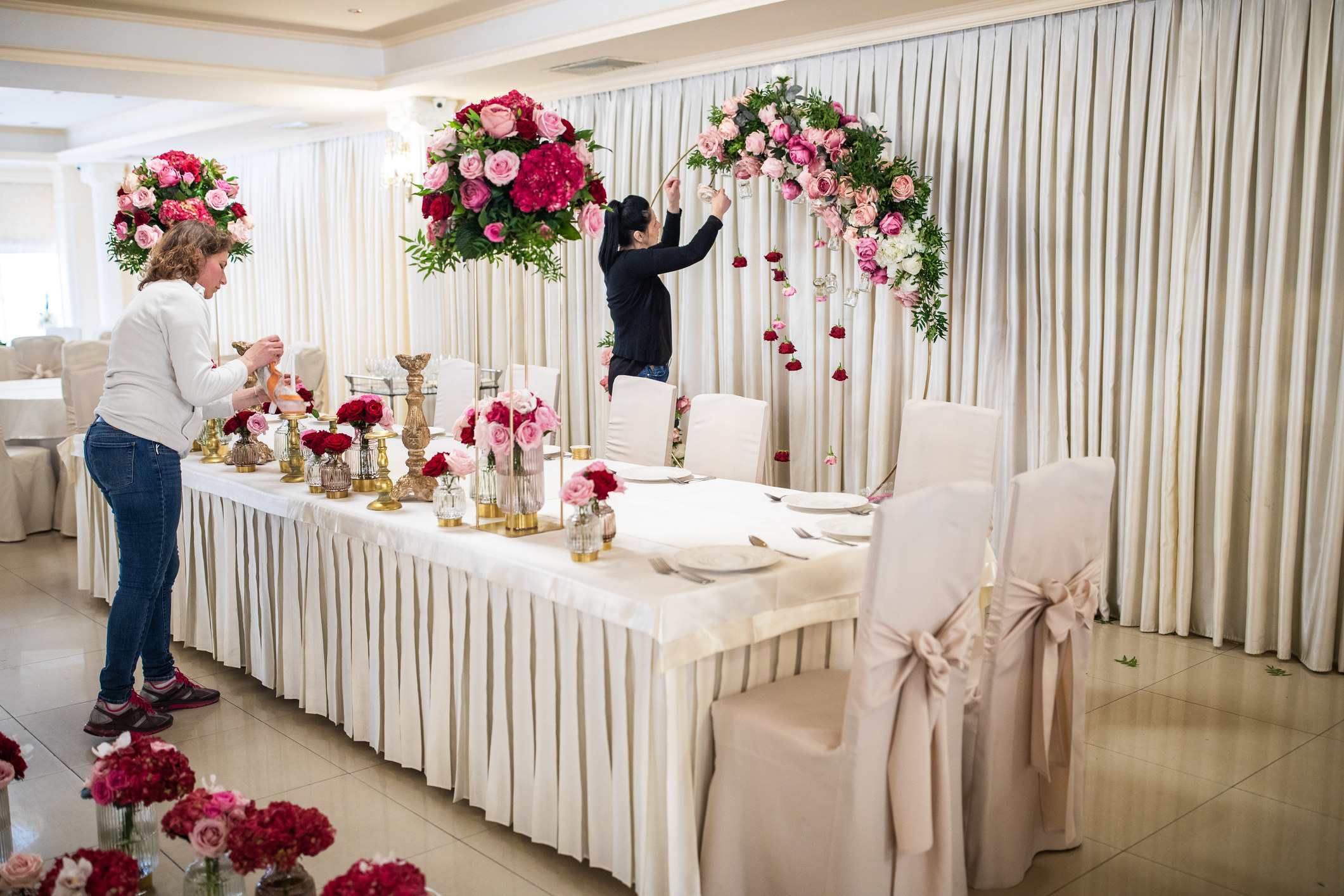 People decorating a venue with flowers