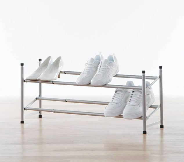 An expandable shoe rack topped with three pairs of shoes