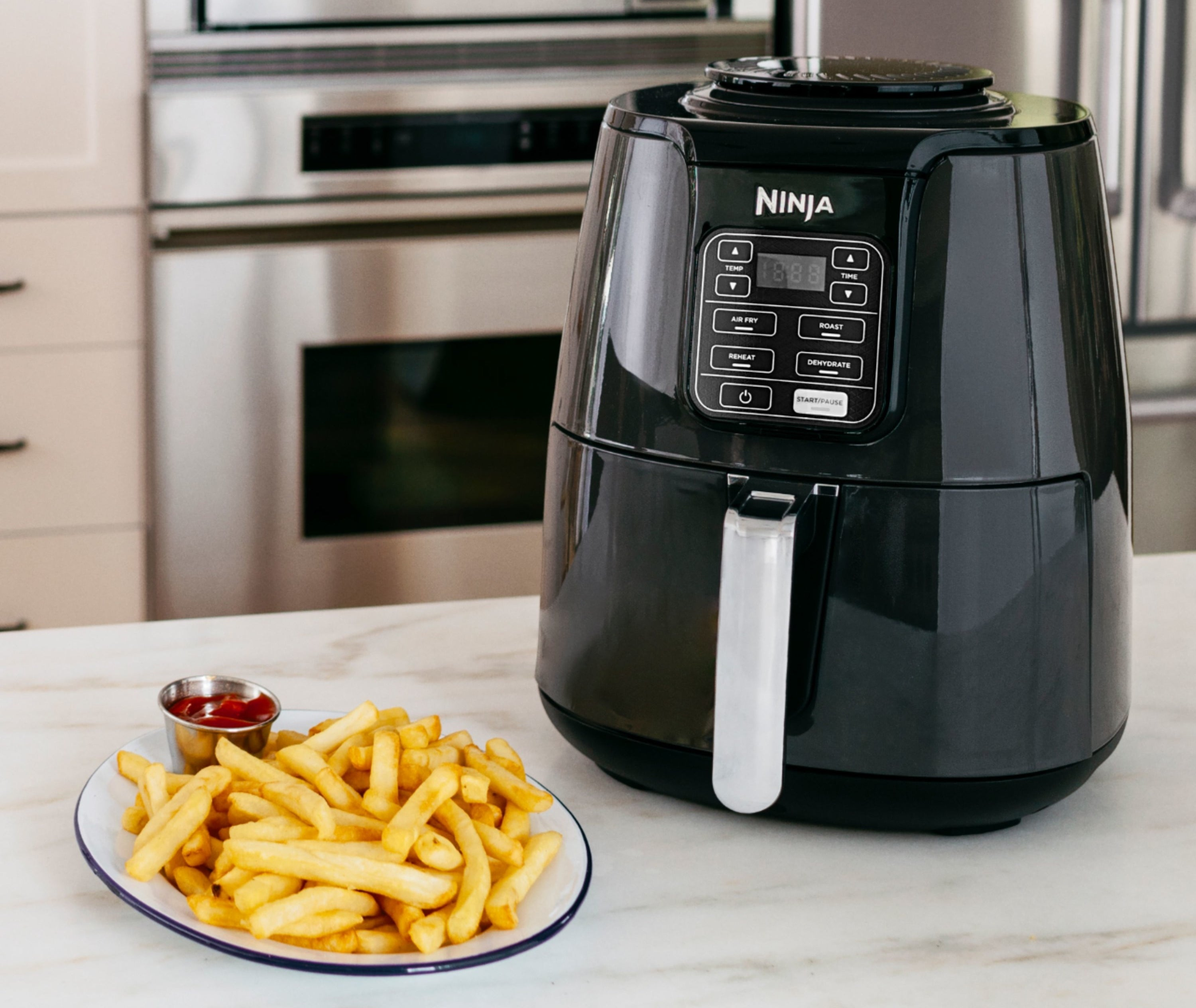the air fryer next to a plate of french fries