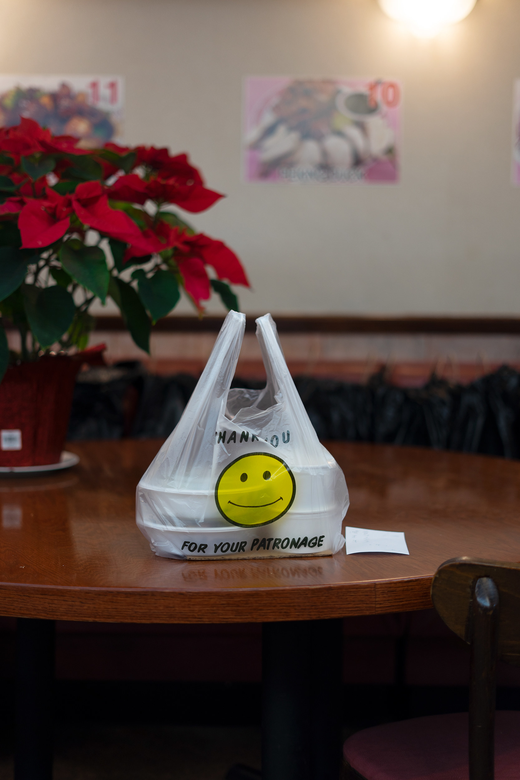 A bag with a smiley face on it at an empty table