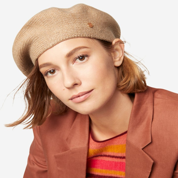 model wears beige beret with a rust blazer and striped shirt