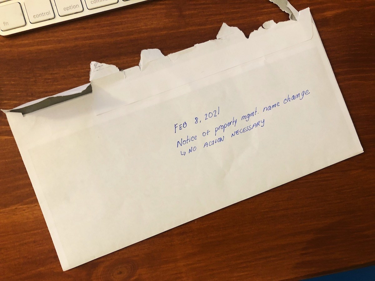 "White envelope on desk with handwritten note on center reading, ""Feb. 8, 2021. Notice of property management name change. No action necessary"""