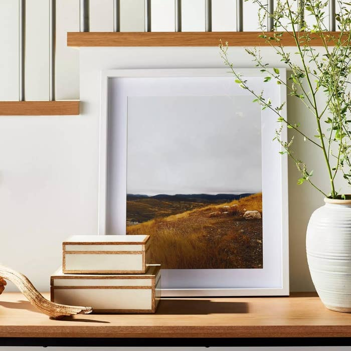 The piece of framed wall art in a white frame