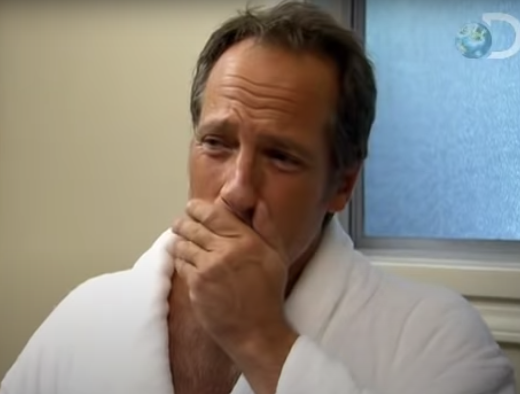 Mike Rowe wearing a bathrobe and holding his hand over his mouth with a perturbed look in his face
