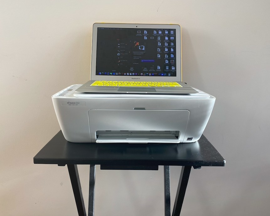 A laptop sits on top of a printer, which is placed on a TV tray.