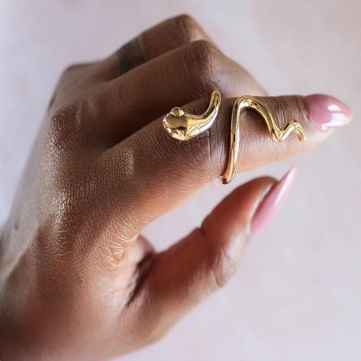 Model wears gold snake-shaped ring on index finger