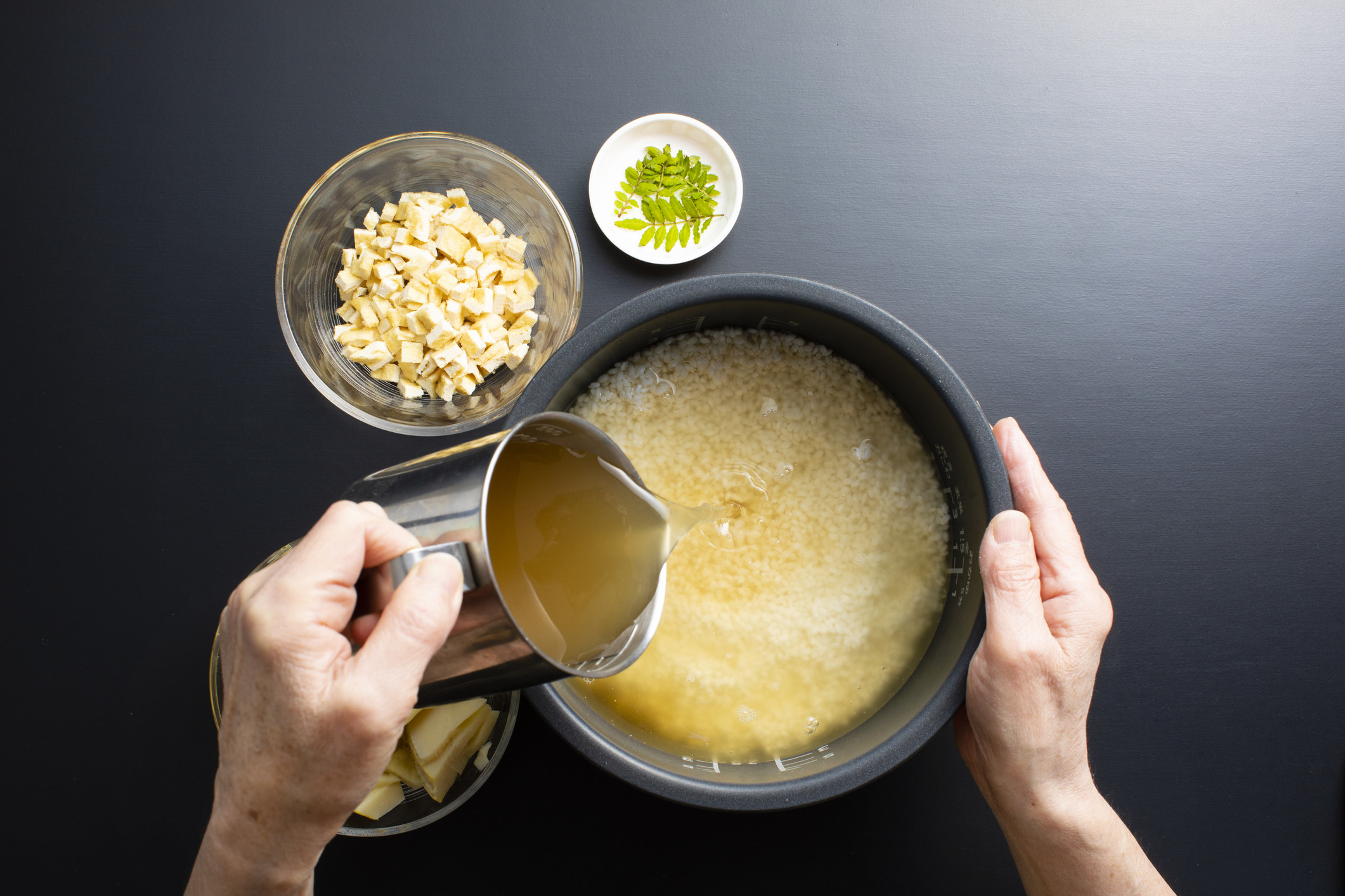 Pouring chicken broth into rice.