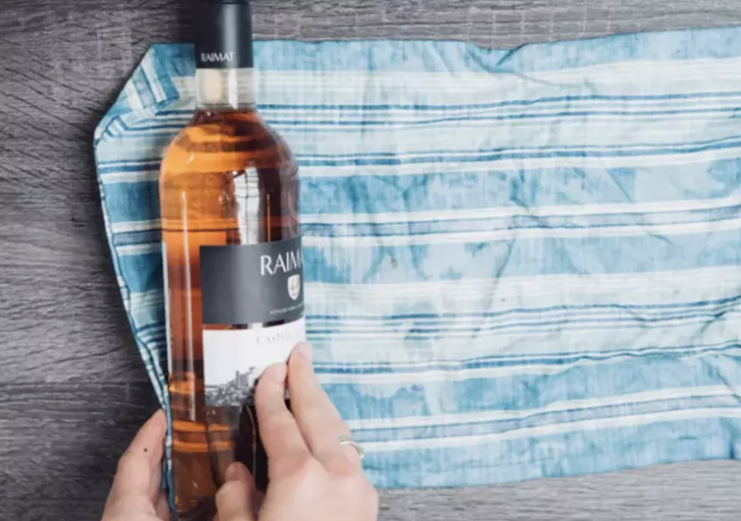 Wrapping a bottle of wine in a dish towel.