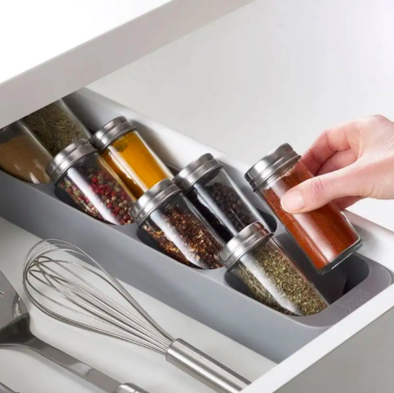 Someone removing a bottle of spices from the angled spice rack