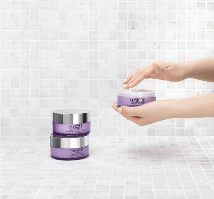 person scooping out the cleansing balm