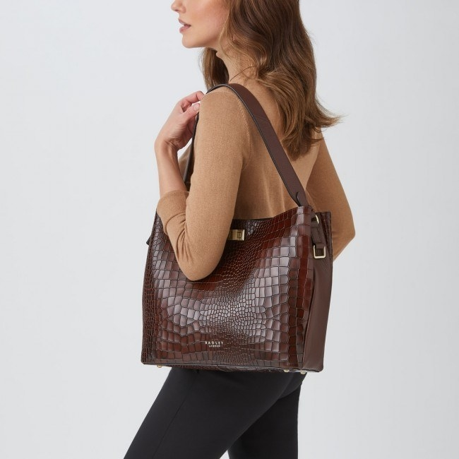 model carrying brown leather tote bag