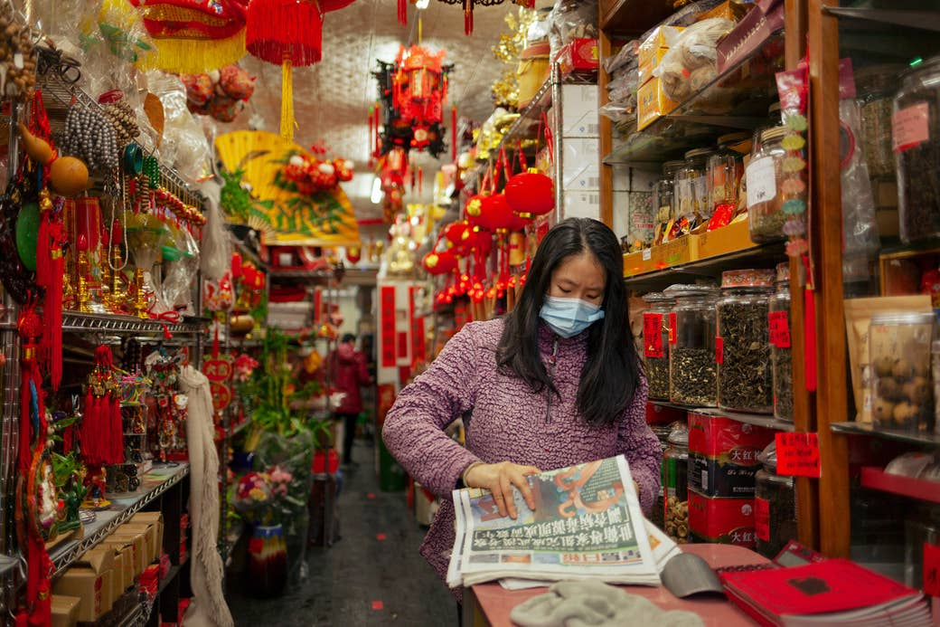 A woman wearing a mask and reading a newspaper in a store in Chinatown