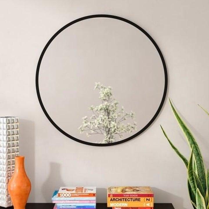 large circular mirror with black frame