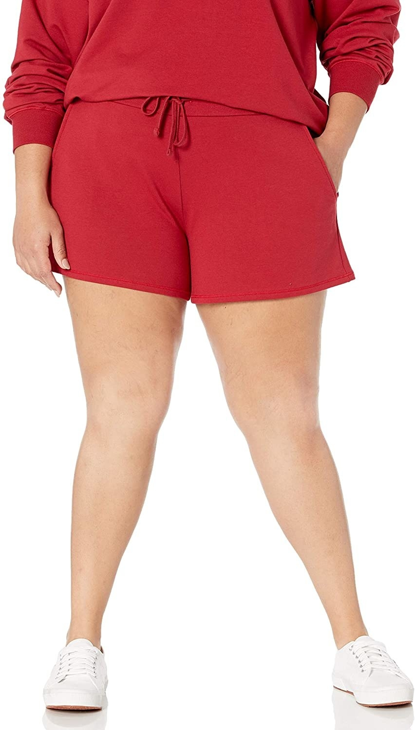 Model wears red shorts with matching sweatshirt and white sneakers