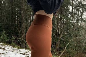 A model wearing the leggings in the snow in the color Rust