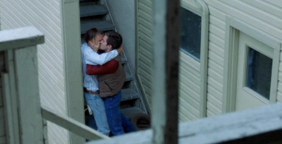 "Jake Gyllenhaal and Heath Ledger's characters sneaking a kiss outside in ""Brokeback Mountain"""