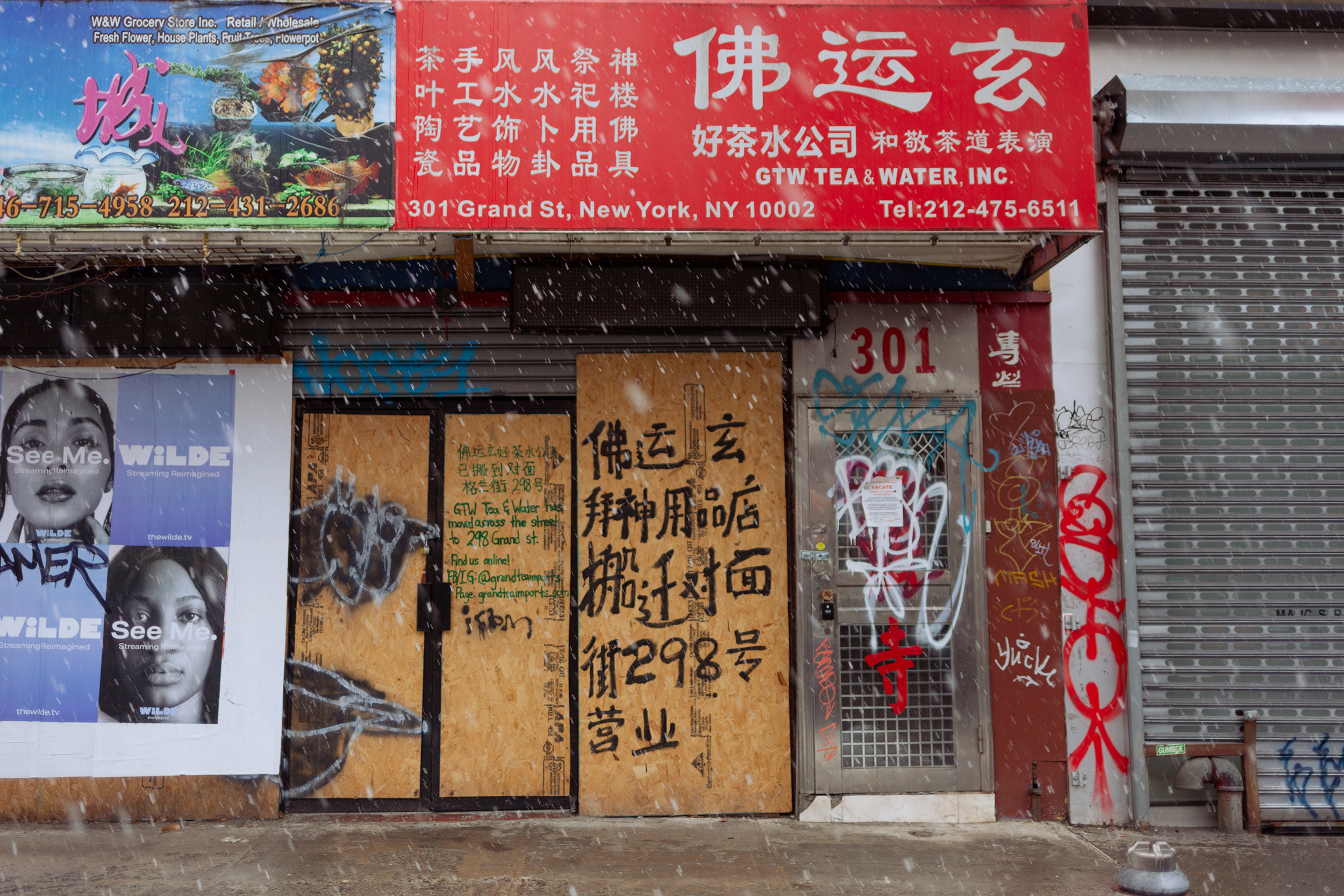 Boarded up stores with chinese characters written in paint on the boards