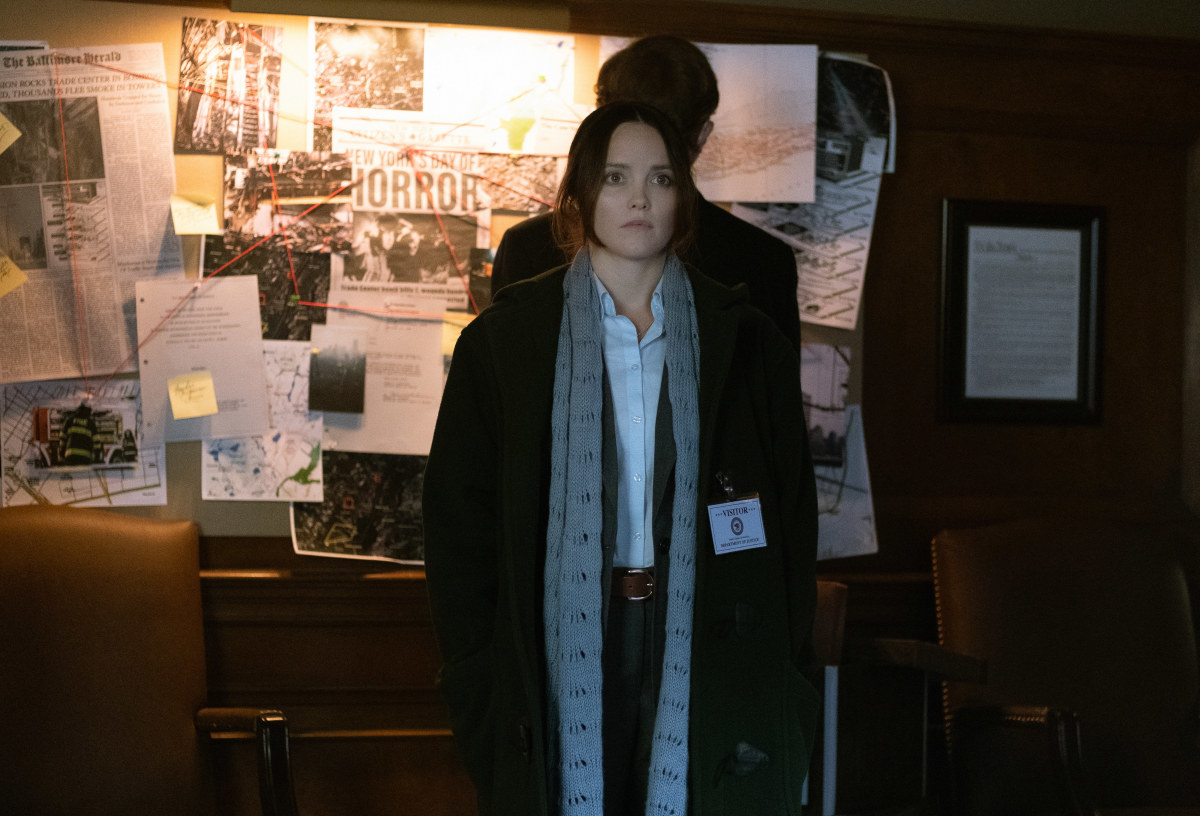 Clarice looking at the camera with a bulletin board of newspaper clippings behind her