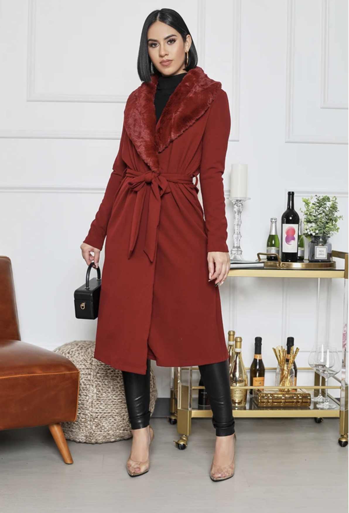 Model in burgundy midi-length tie-waist cardigan with a faux fur collar