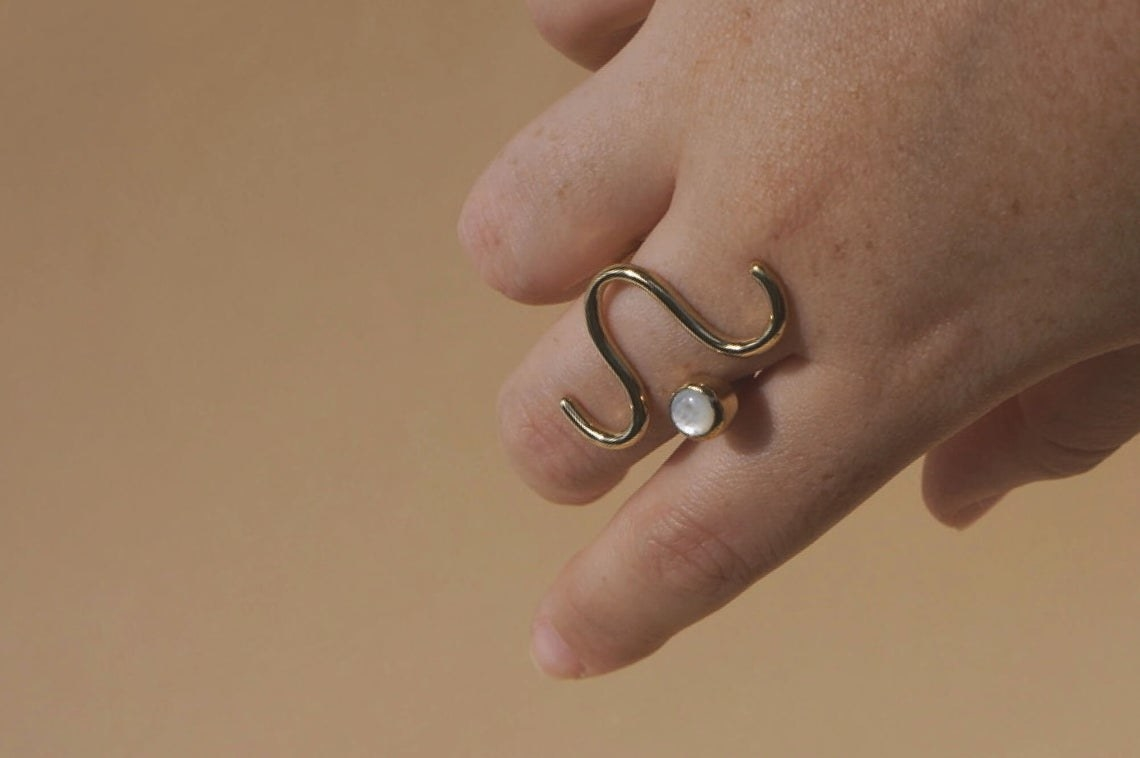 ring with brass squiggle and shiny white stone