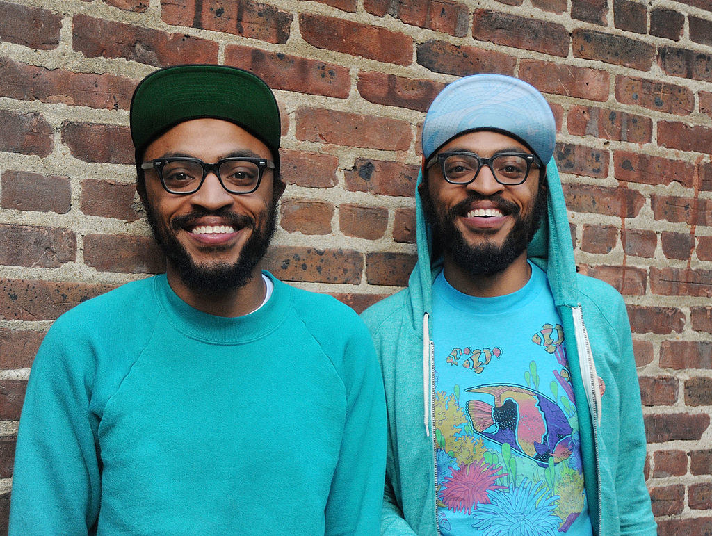 Kenny Lucas and Keith Lucas wearing glasses, hats, and smiling