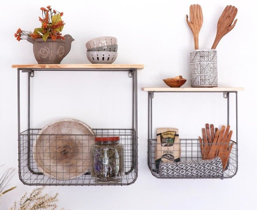 Two different sizes wooden shelves with connected wire storage baskets underneath filled with kitchen supplies