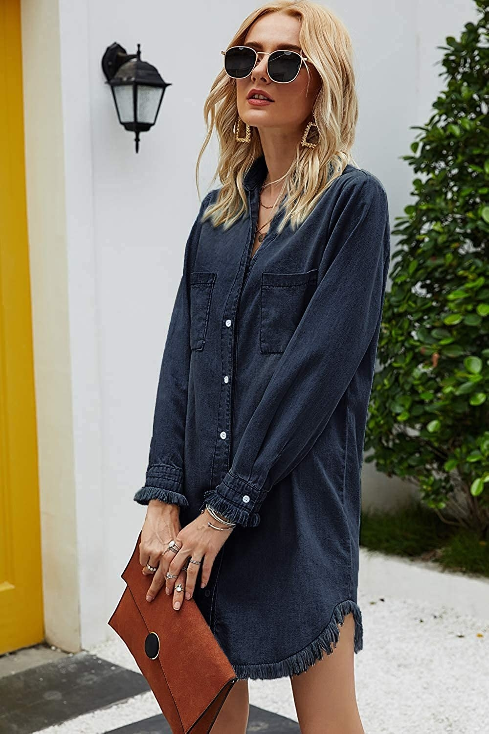 A model wearing the long-sleeved mini dress with frayed cuffs in dark wash denim