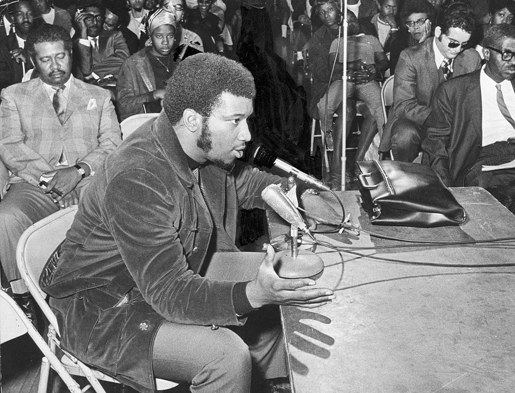 1969 black and white photo of Black Panther Fred Hampton testifying at a meeting