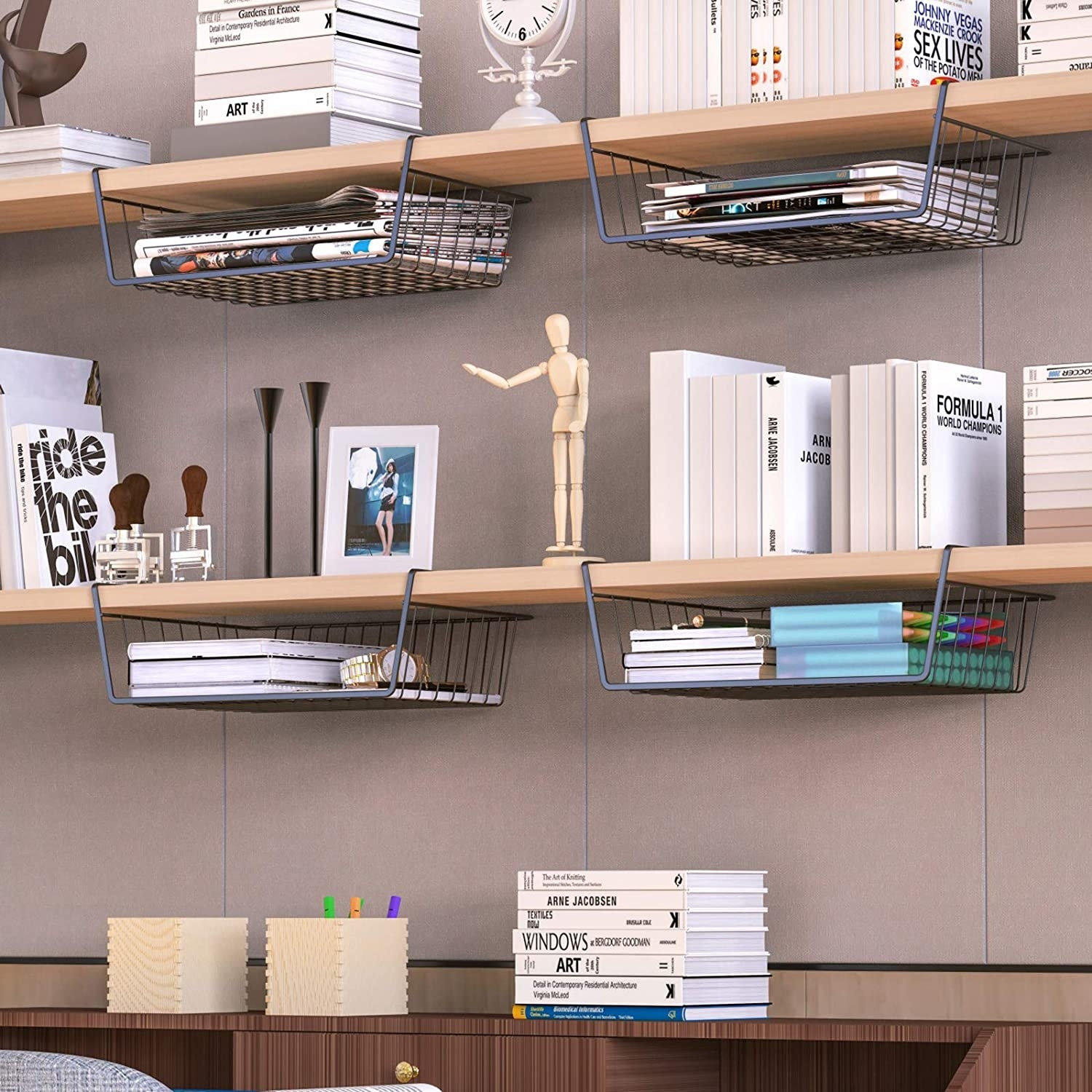 The baskets holding notebooks and stationery and hanging under a bookshelf