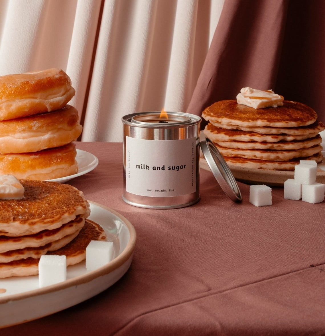 A candle surrounded by plates of pancakes