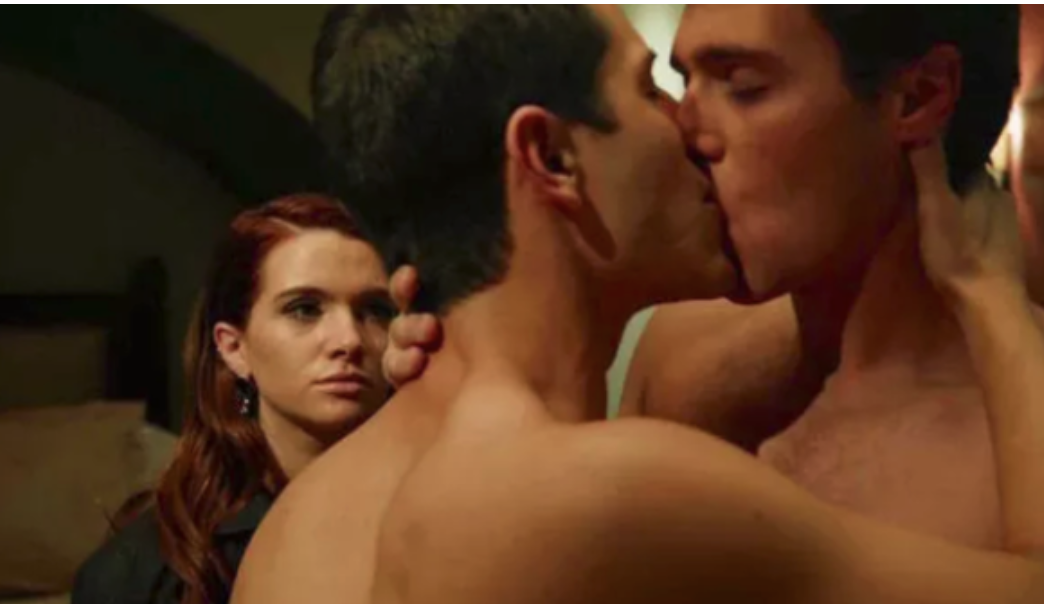 Two guys kissing while a friend watches in an MTV scripted series