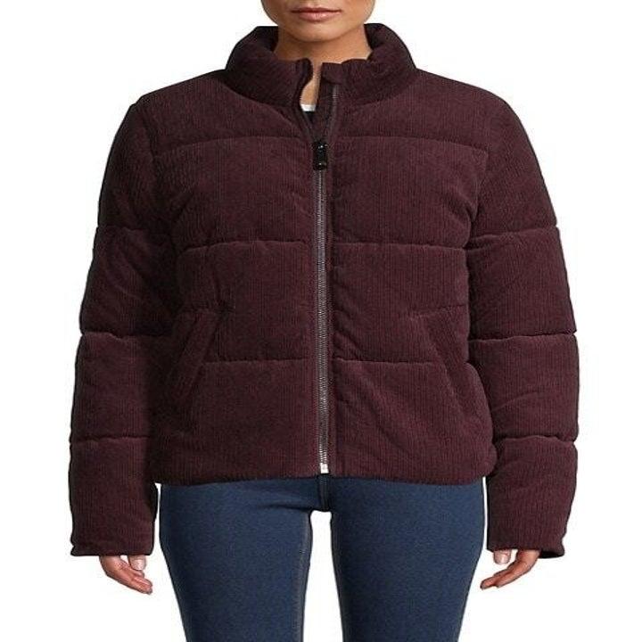 Model wears dark red puffer jacket with blue jeans