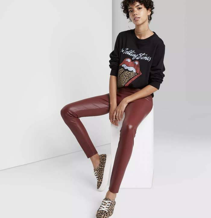 A model wearing red stretchy leather leggings with a black sweater
