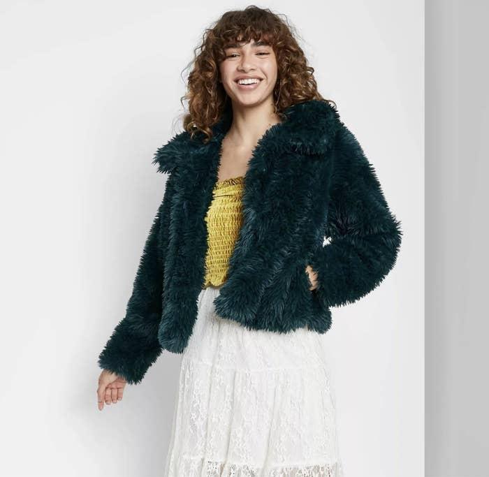A model wearing a dark green fur coat