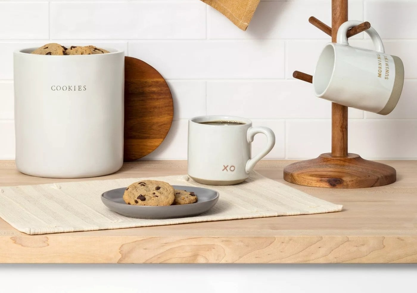 cookie jar next to mug and plate on counter