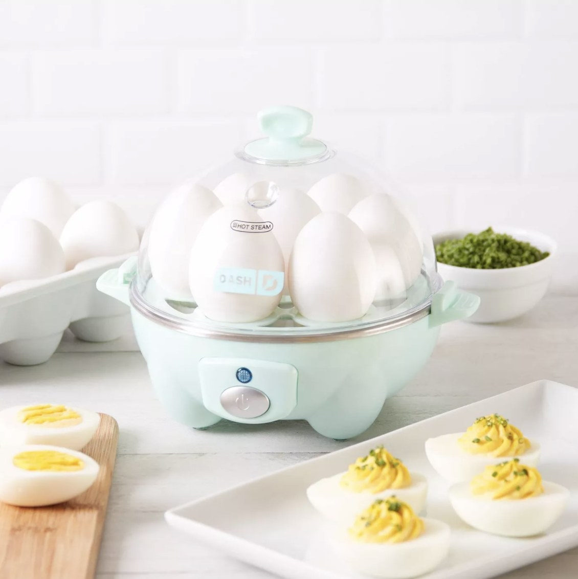 the egg cooker in aqua surrounded by eggs