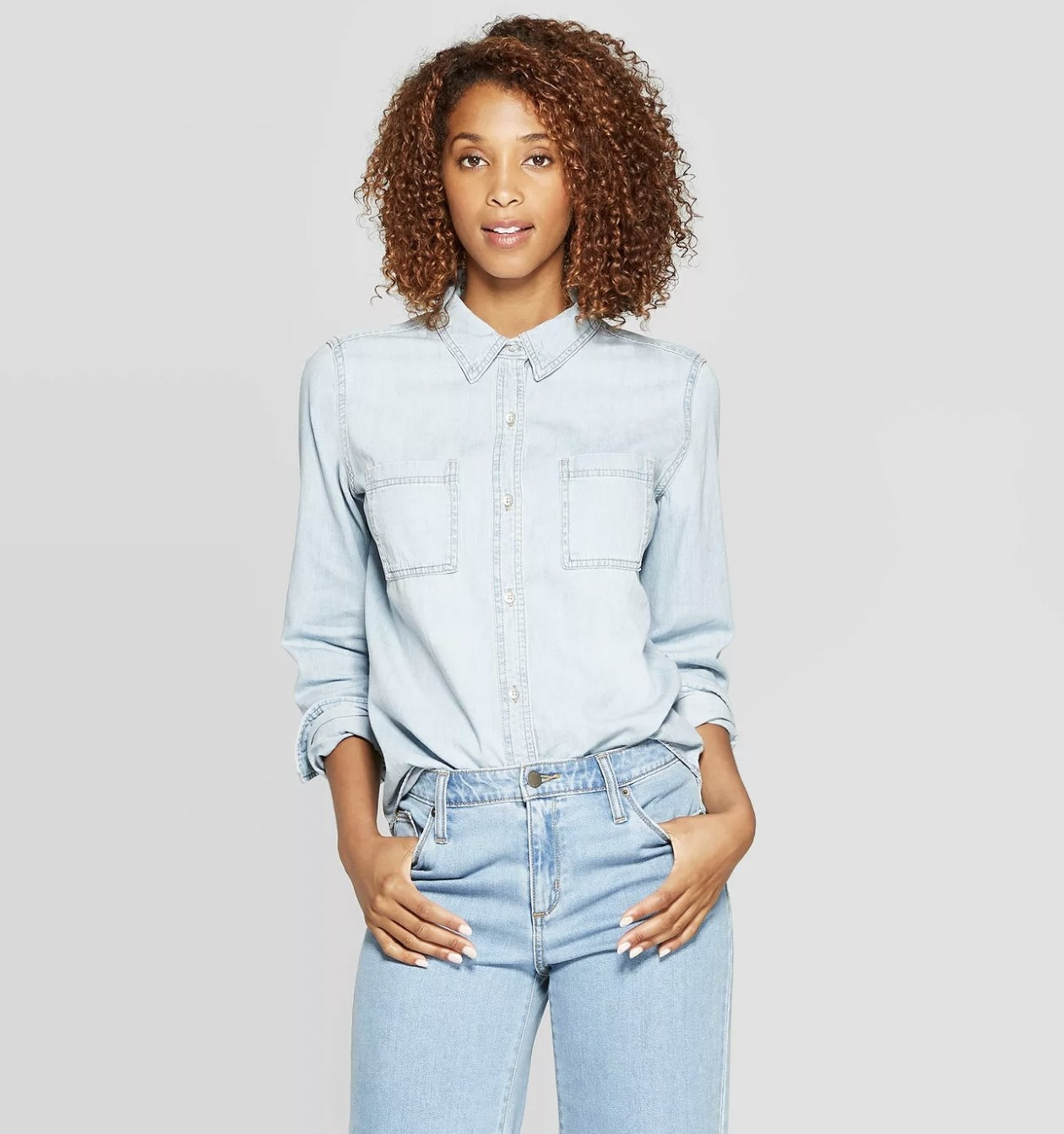 A model wearing a long-sleeved denim shirt with blue jean
