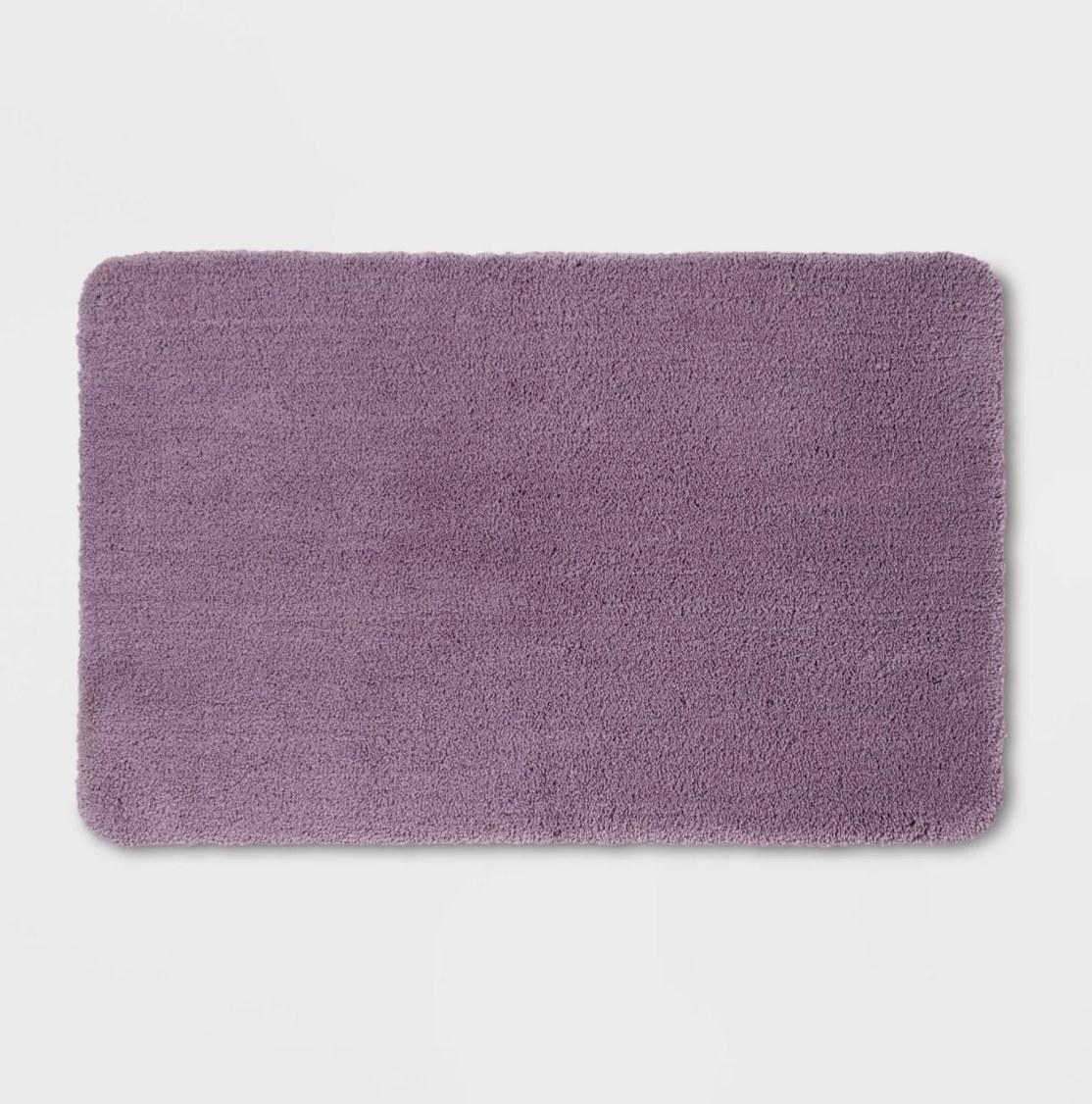 a purple plush bath mat