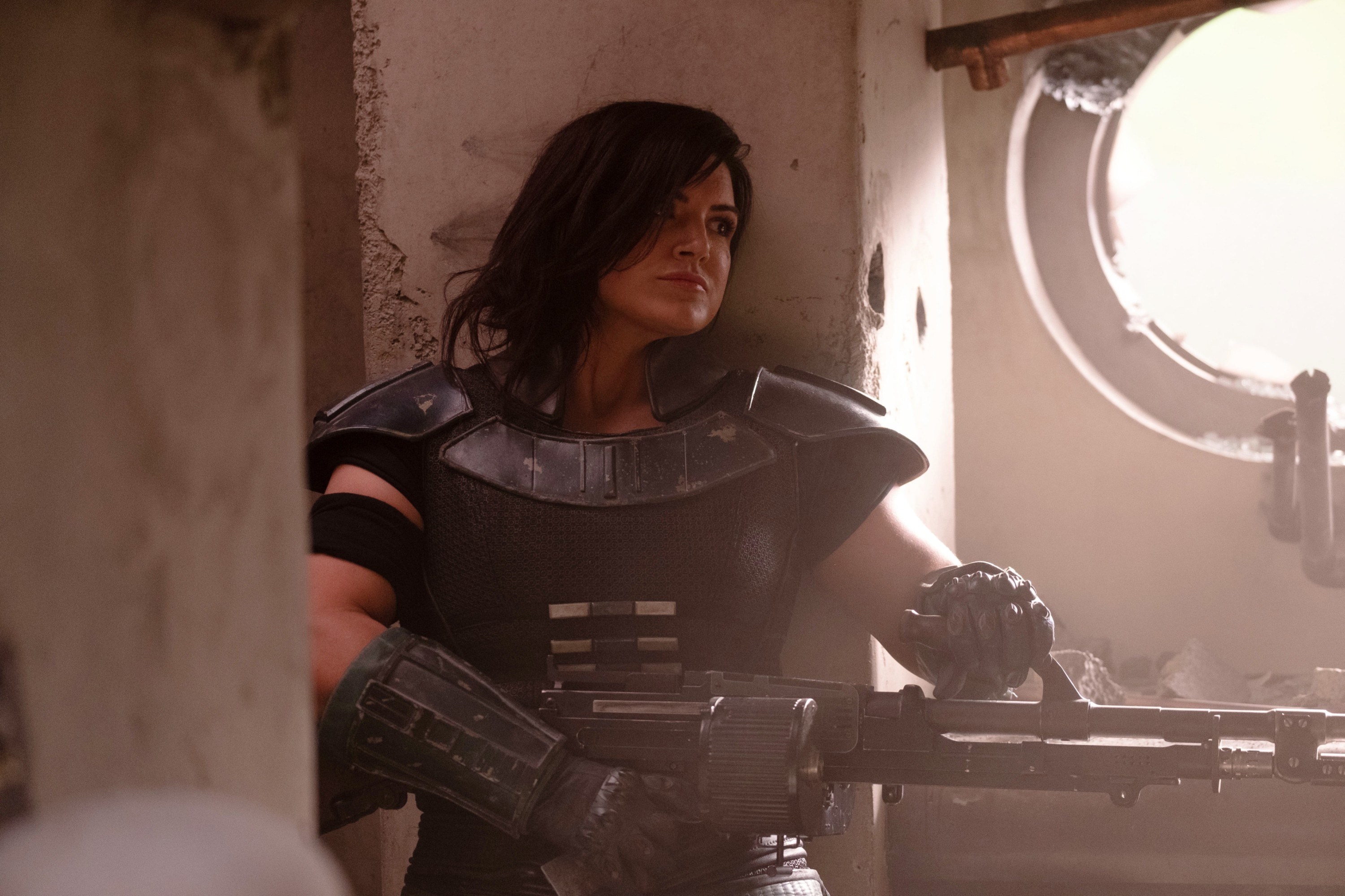 Gina Carano leans against a wall with a gun in The Mandalorian