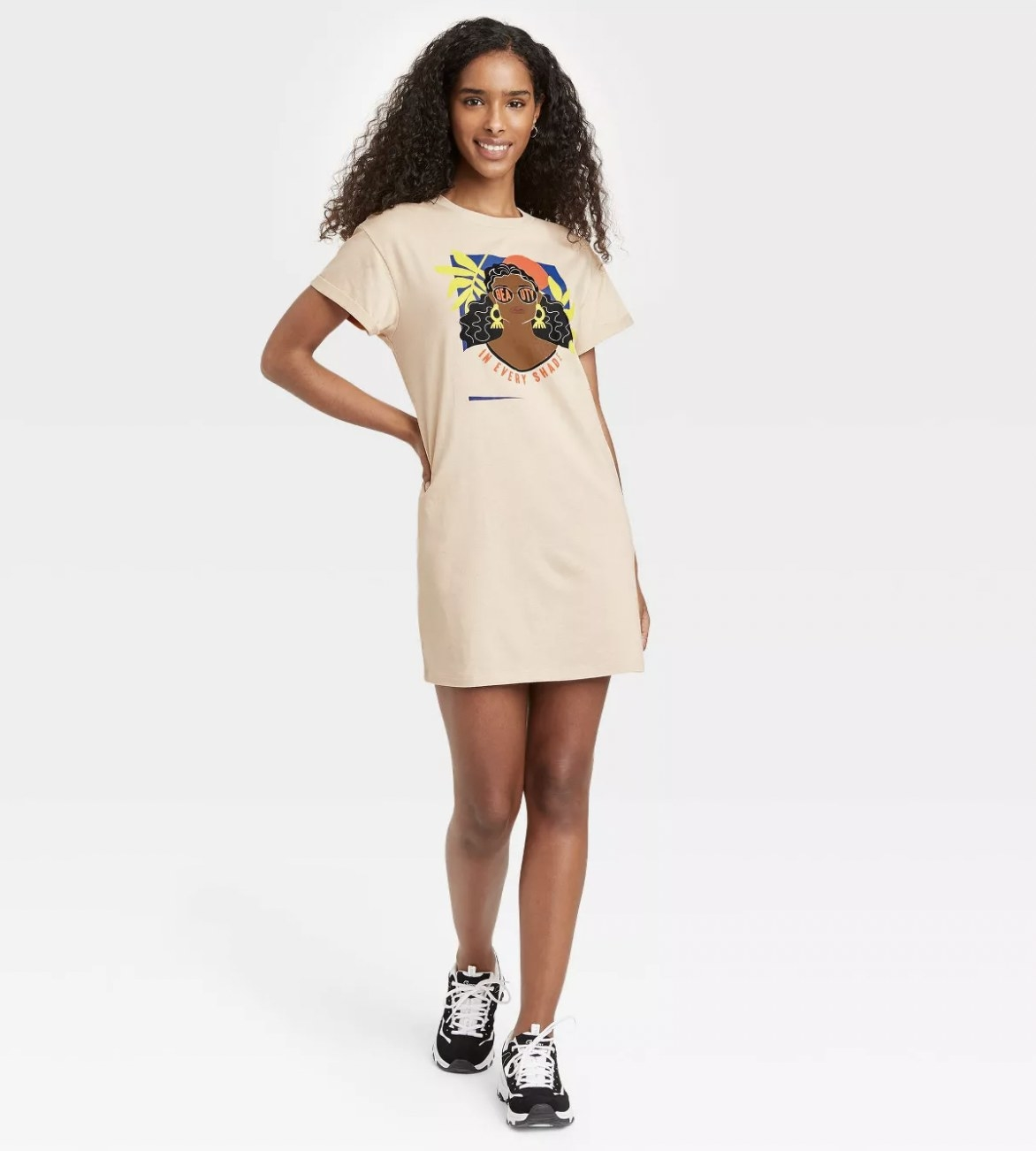 A model wearing a T-shirt dress with an African American woman graphic