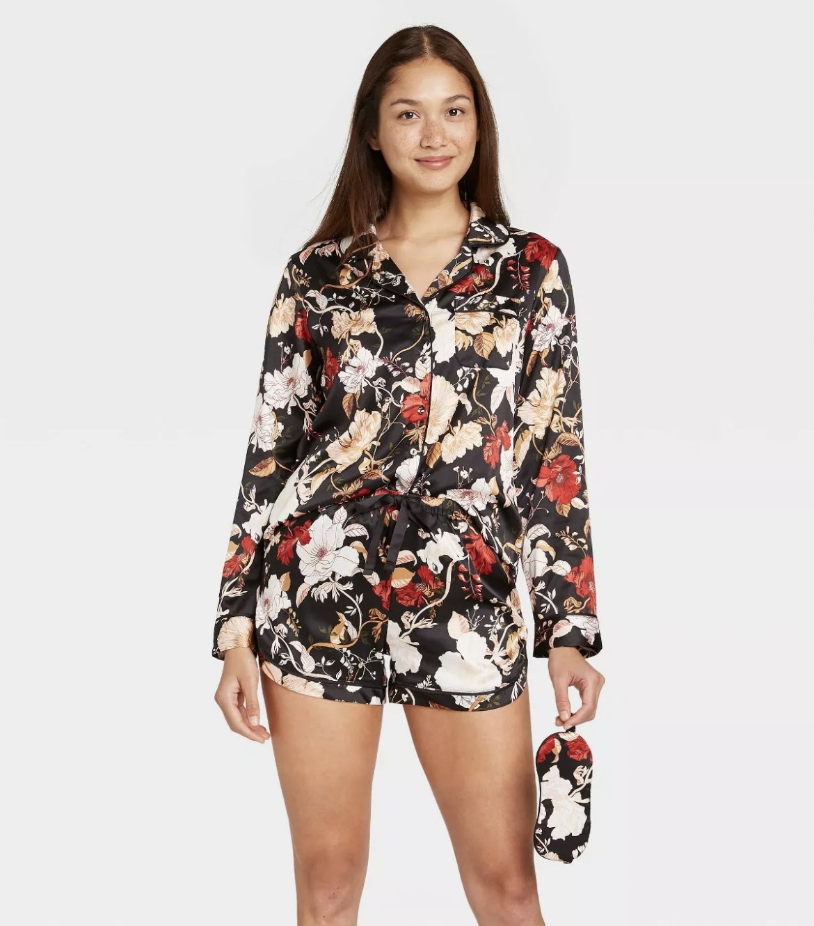 A model wearing a black, red, and white floral print pajama short set